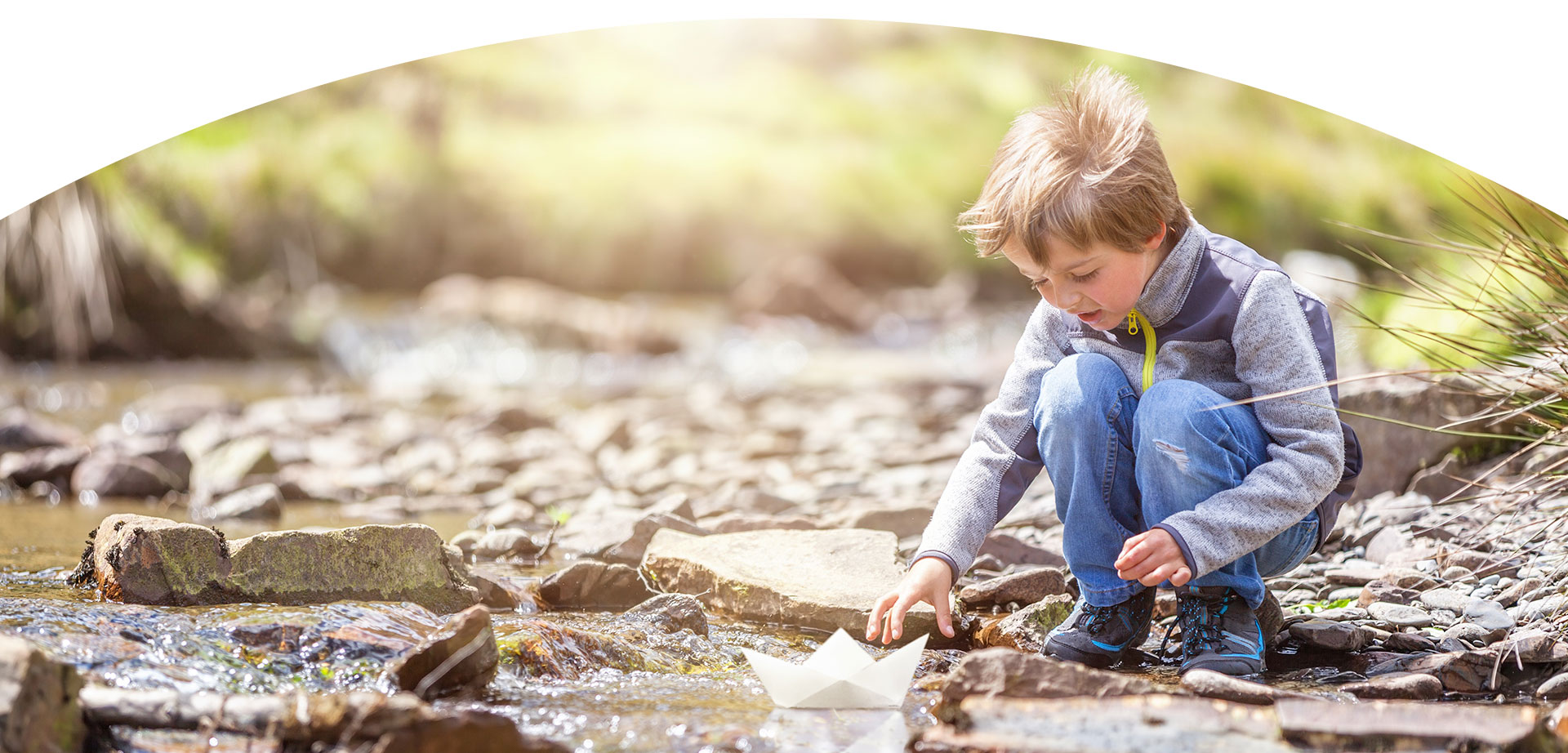 Boy sailing a paper boat in the creek